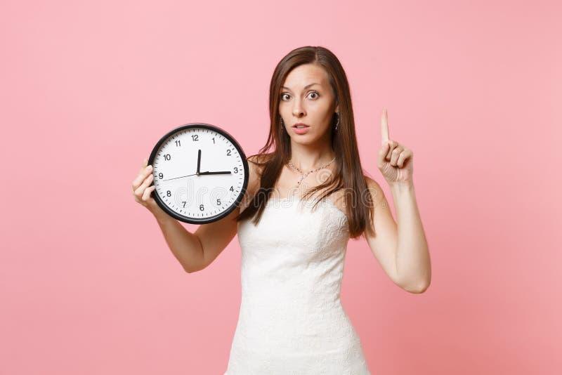 Bekymrad brudkvinna i bröllopsklänning som pekar pekfingret upp att rymma den runda ringklockan på rosa bakgrund royaltyfri foto