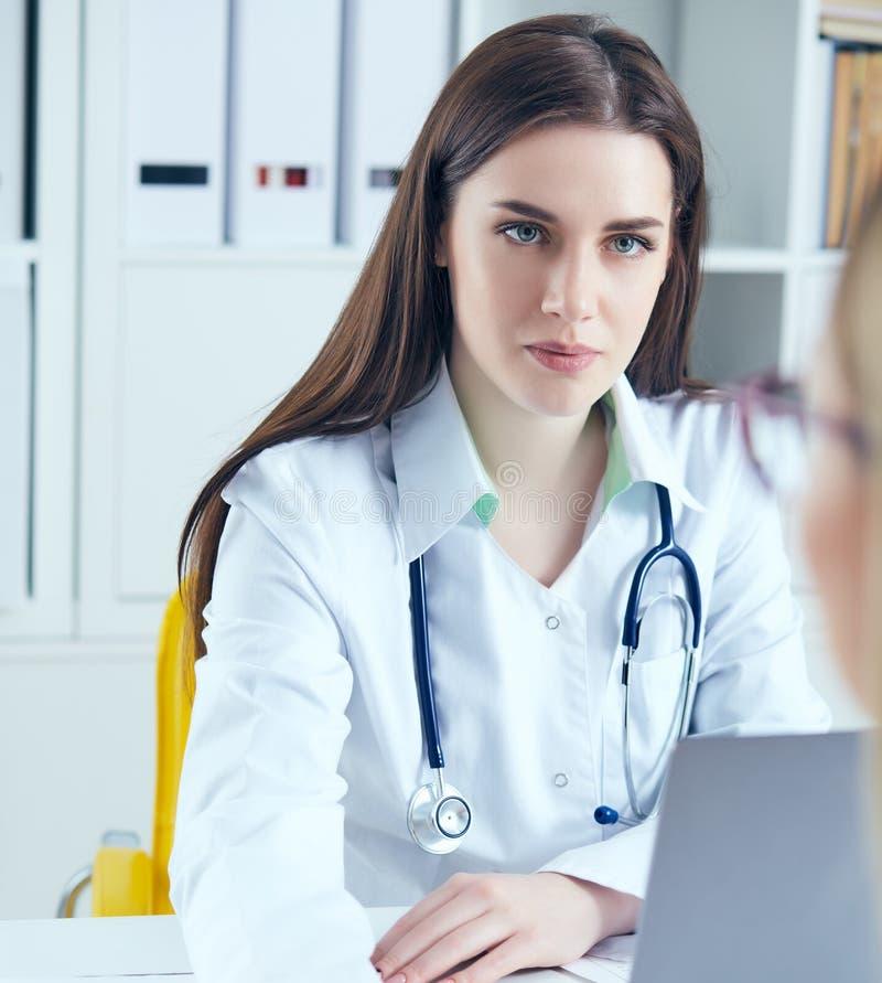Bekymrad härlig kvinnlig medicindoktor som lyssnar försiktigt tålmodiga klagomål i medicinskt kontor Medicinsk vård eller royaltyfria foton