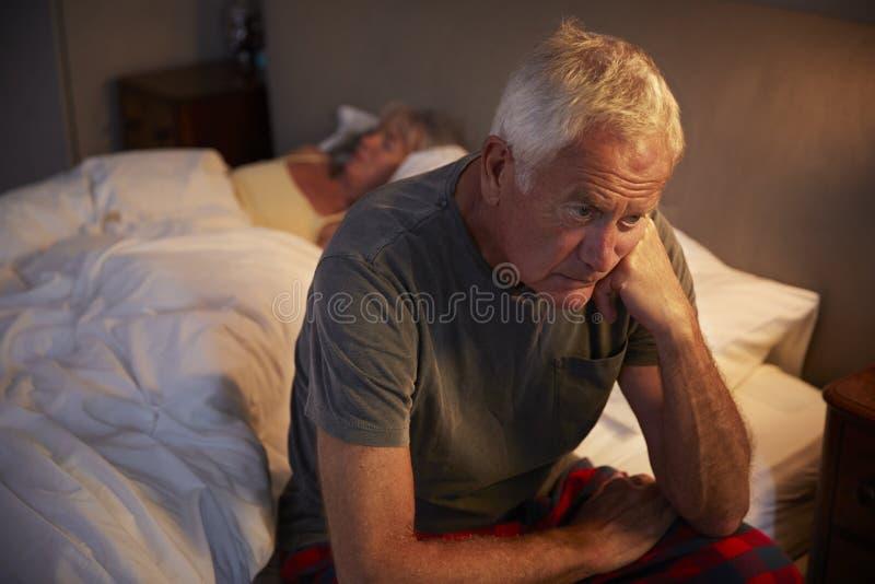 Bekymrad hög man i säng på nattlidande med sömnlöshet royaltyfria bilder