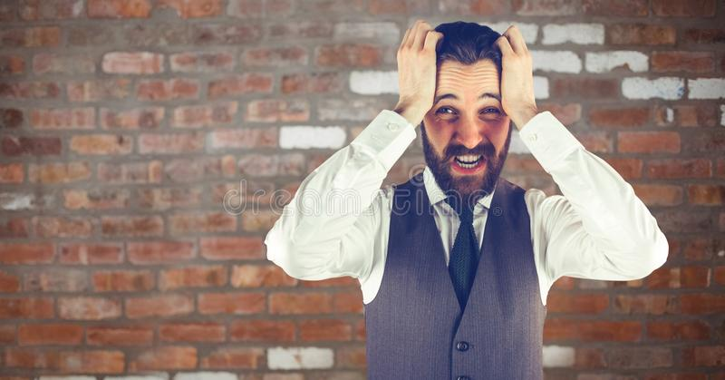 Bekymrad hipsterman med hans händer på hans huvud framme av en röd vägg arkivfoto