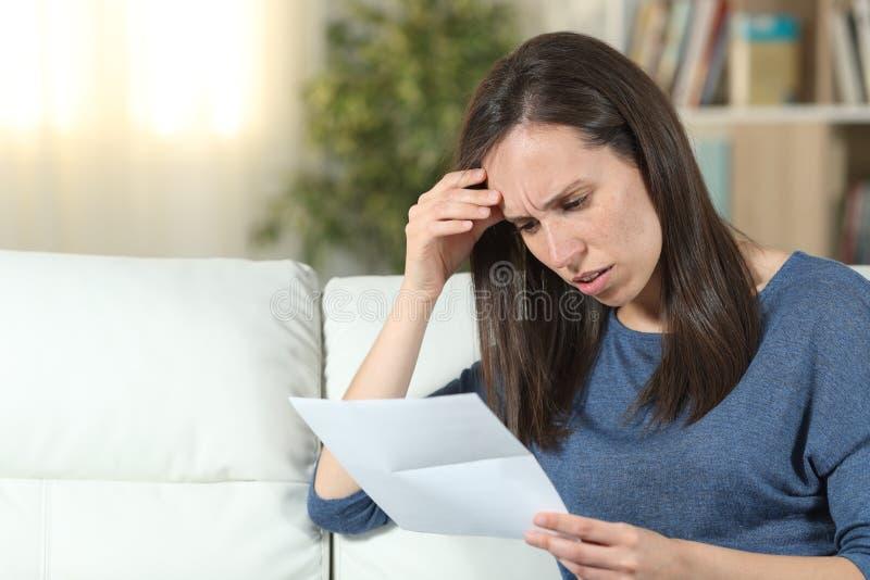 Bekymrad kvinna som hemma läser ett brev på en soffa royaltyfria foton