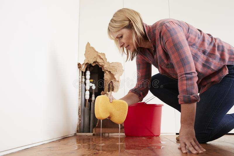 Bekymrad kvinna som moppar upp vatten från ett bristningsrör med svampen royaltyfria bilder
