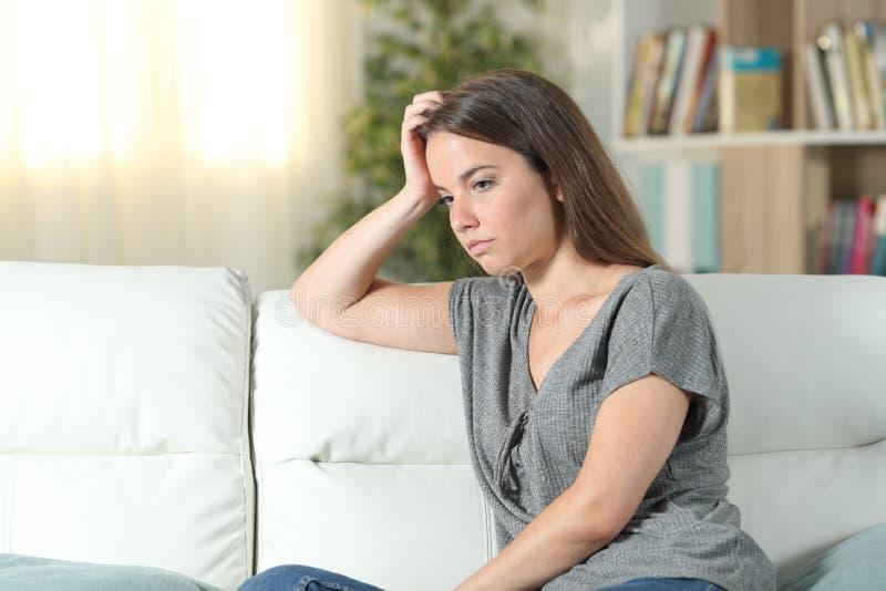 Bekymrad kvinna som ser bort på en soffa hemma royaltyfri fotografi