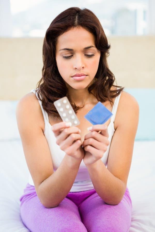 Bekymrad kvinna som ser det att använda preventivmedel fotografering för bildbyråer