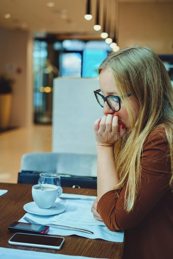 Bekymrad kvinna som ser mobiltelefonen i en restaurang royaltyfria bilder