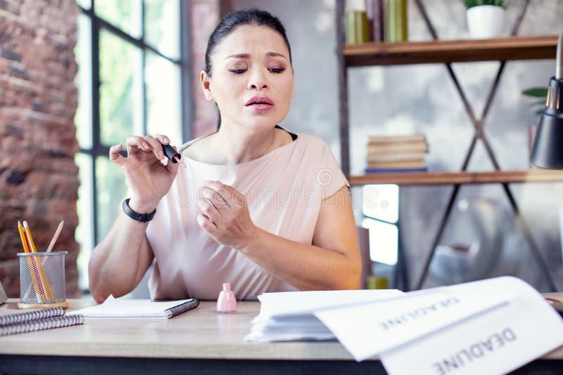 Bekymrad kvinnlig anställdmålning spikar arkivfoto