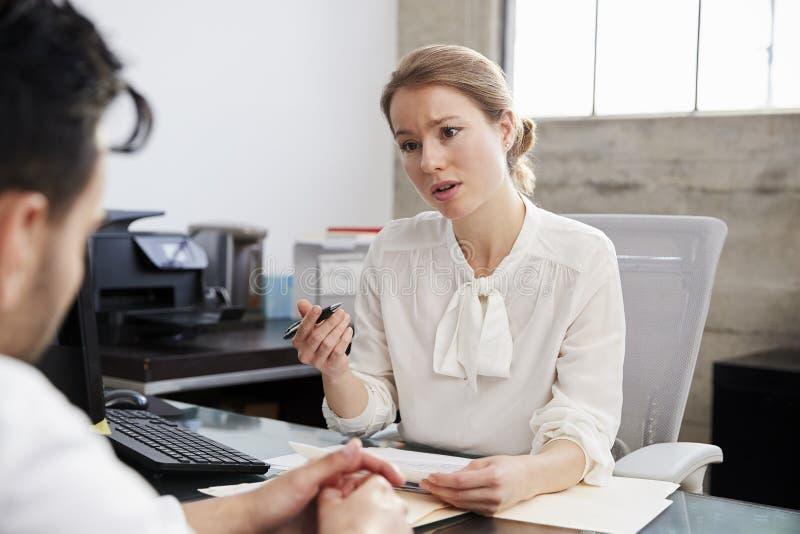Bekymrad kvinnlig terapeut i konsultation med den manliga patienten arkivfoto