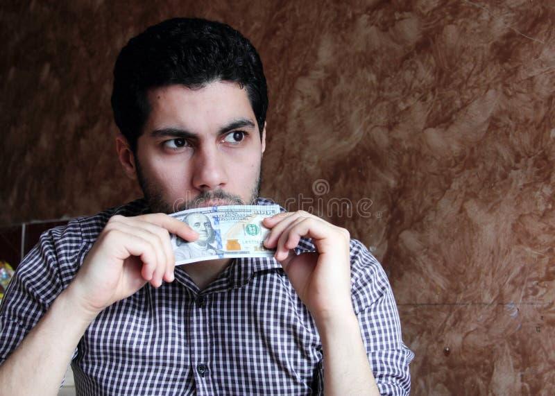 bekymrad ledsen arabisk ung affärsman med dollarräkningen arkivbild