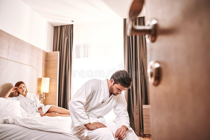 Bekymrad man för svaghet i hotellrum Mannen kan inte göra könsbestämmer med hans kvinna fotografering för bildbyråer