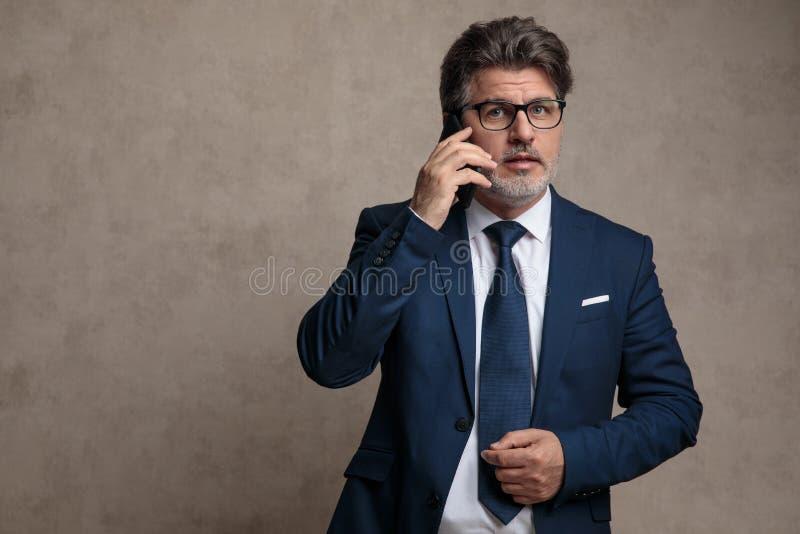 Bekymrad man som talar p? telefonen royaltyfria bilder