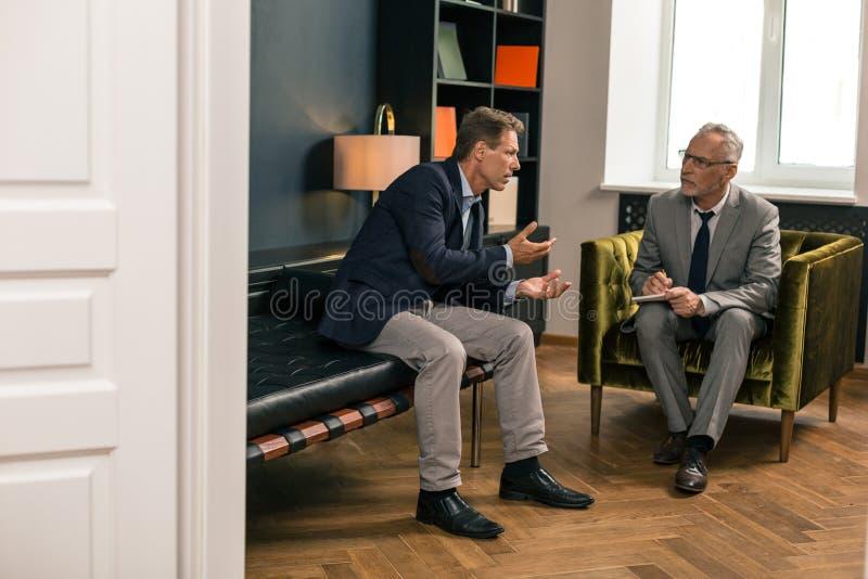 Bekymrad medelålders man som talar till hans uppmärksamma psykoterapeut royaltyfri bild