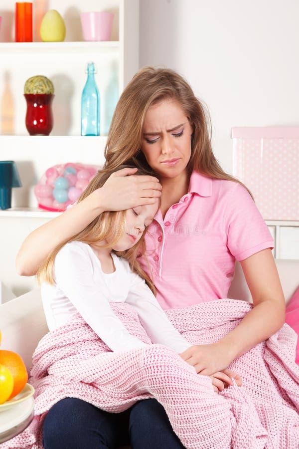 Bekymrad moder med det sjuka barnet arkivfoto