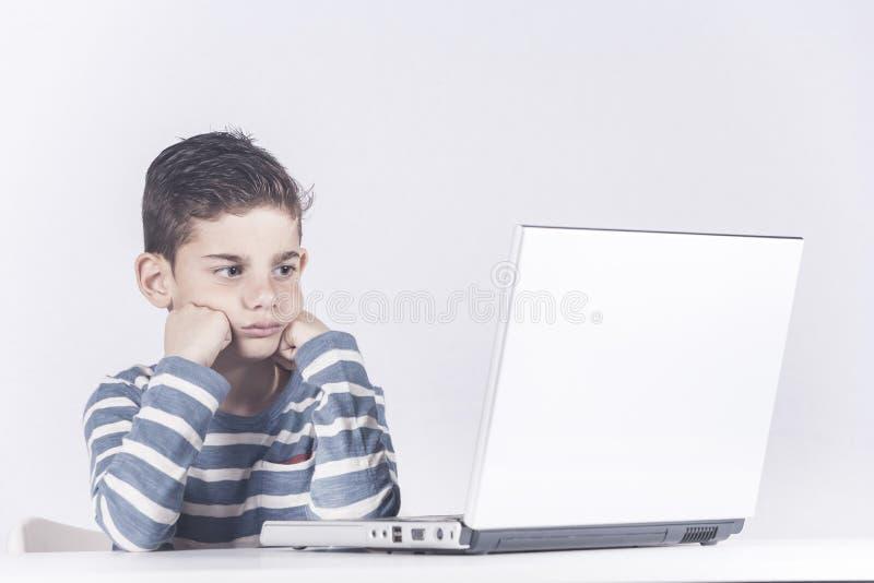 Bekymrad pojke som använder en bärbar datordator royaltyfri bild