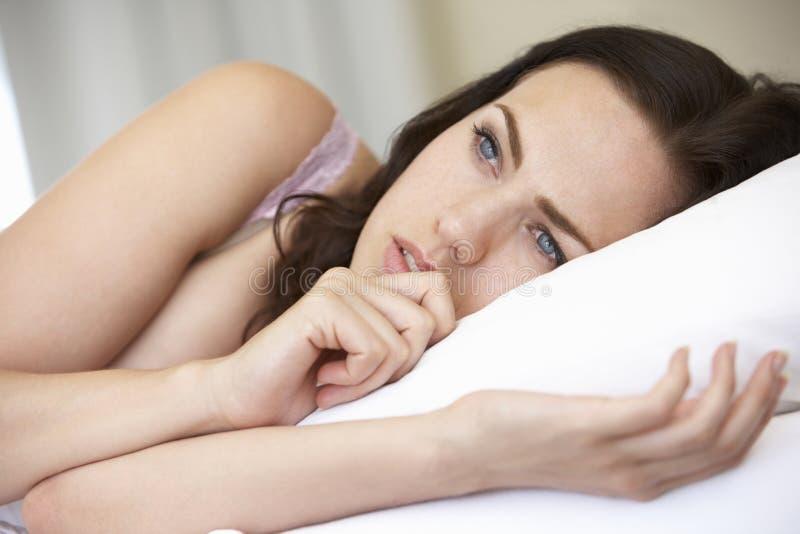 Bekymrad seende ung kvinna på säng royaltyfri bild