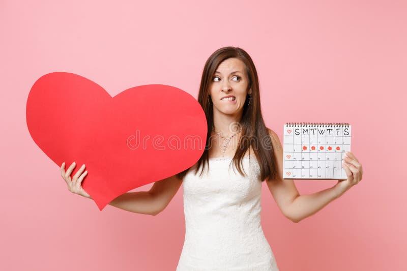 Bekymrad skyldig brudkvinna i kalendern för perioder för tom tom röd hjärta för bröllopsklänninghåll den kvinnliga för att kontro arkivbild