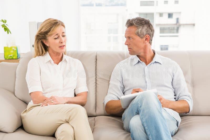 Bekymrad terapeut som lyssnar till den kvinnliga patienten royaltyfria foton