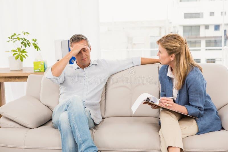 Bekymrad terapeut som talar med den manliga patienten royaltyfri foto