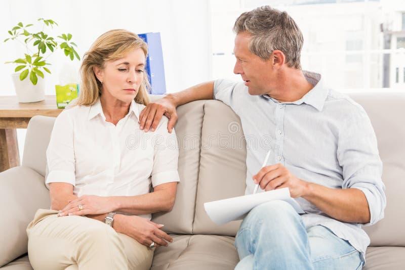 Bekymrad terapeut som tröstar den kvinnliga patienten royaltyfria foton