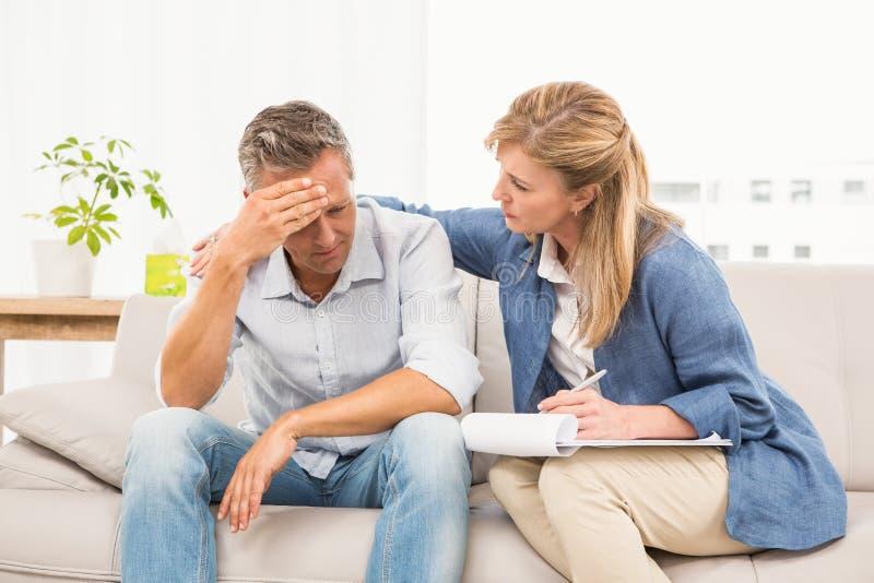 Bekymrad terapeut som tröstar den manliga patienten arkivfoton