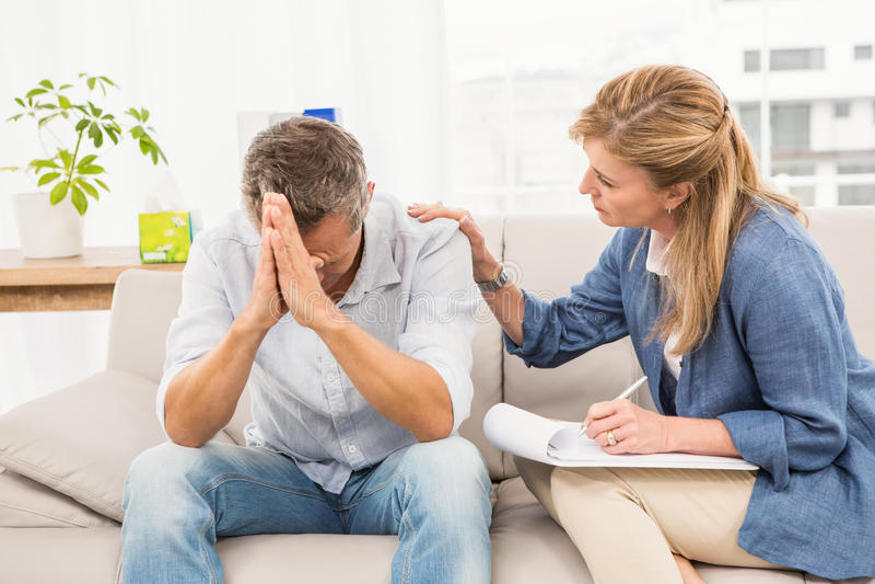 Bekymrad terapeut som tröstar den manliga patienten royaltyfri fotografi