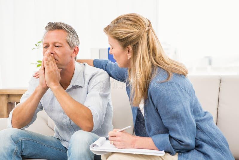 Bekymrad terapeut som tröstar den manliga patienten royaltyfria bilder