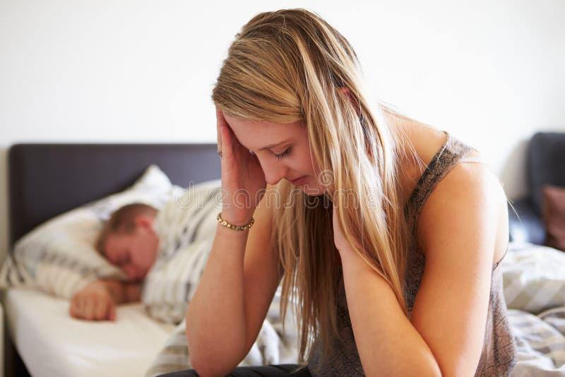 Bekymrad tonårs- flicka i sovrum med pojkvännen royaltyfria bilder