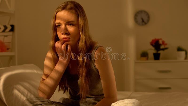 Bekymrad tonårs- flicka som bara sitter i sovrum och tänker och att lida spänning royaltyfri fotografi