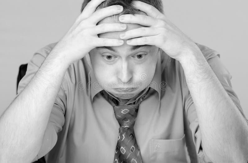 Bekymrad trött affärsman som rymmer hans huvud royaltyfria foton