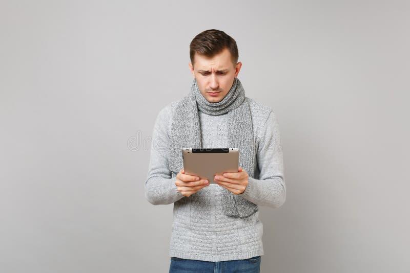 Bekymrad ung man i den gråa tröjan, halsduk genom att använda minnestavlaPCdatoren på grå väggbakgrund i studio Sunt arkivbilder
