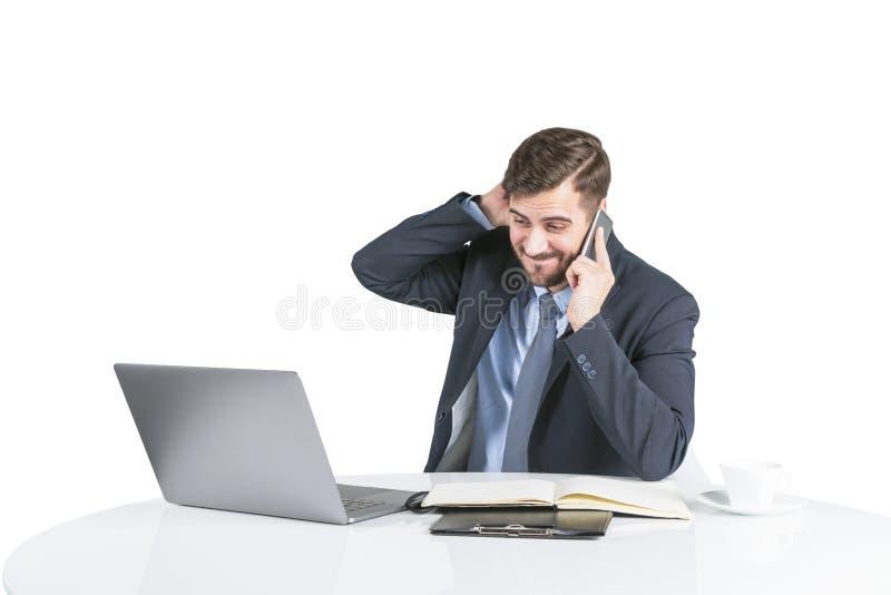 Bekymrad ung man i dräkt på telefonen på tabellen royaltyfri foto