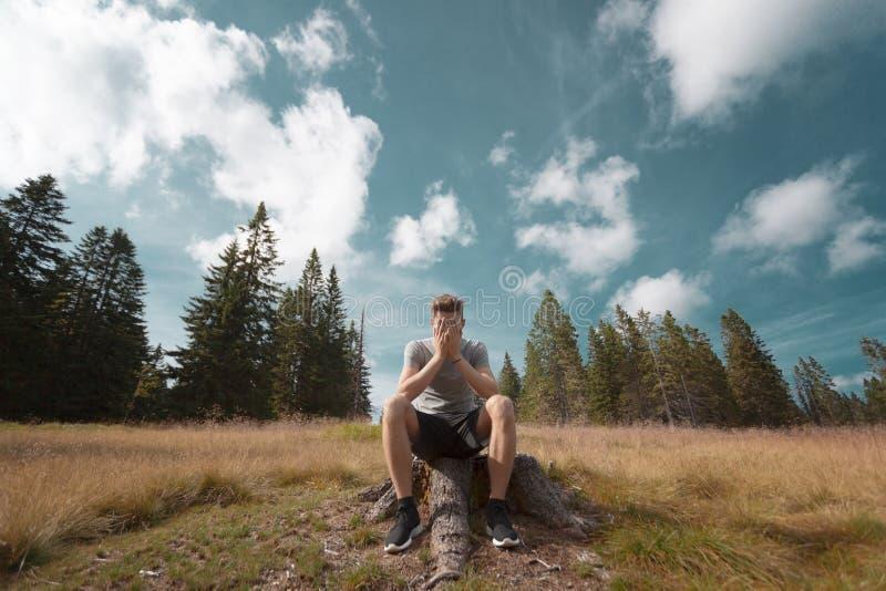 Bekymrad ung man på trädstubbe royaltyfri foto