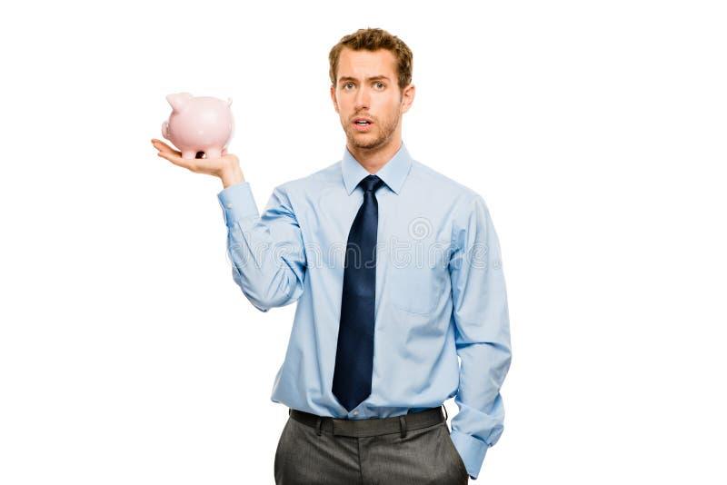 Bekymrad ung man som sätter pengar i den isolerade spargrisen på vit royaltyfri foto