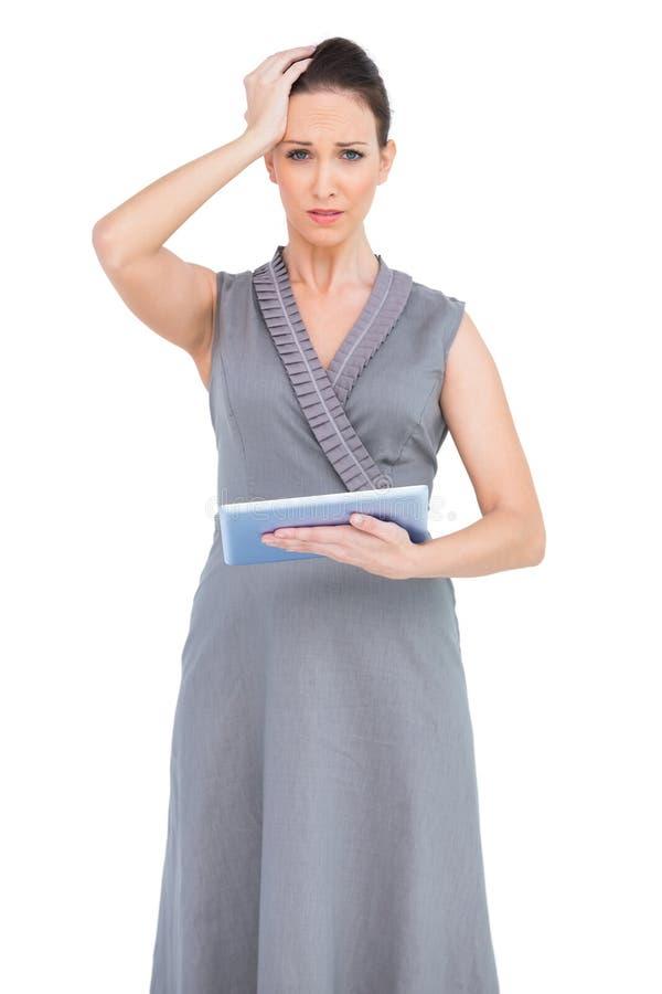 Bekymrad ursnygg kvinna som rymmer den digitala minnestavlan royaltyfria bilder