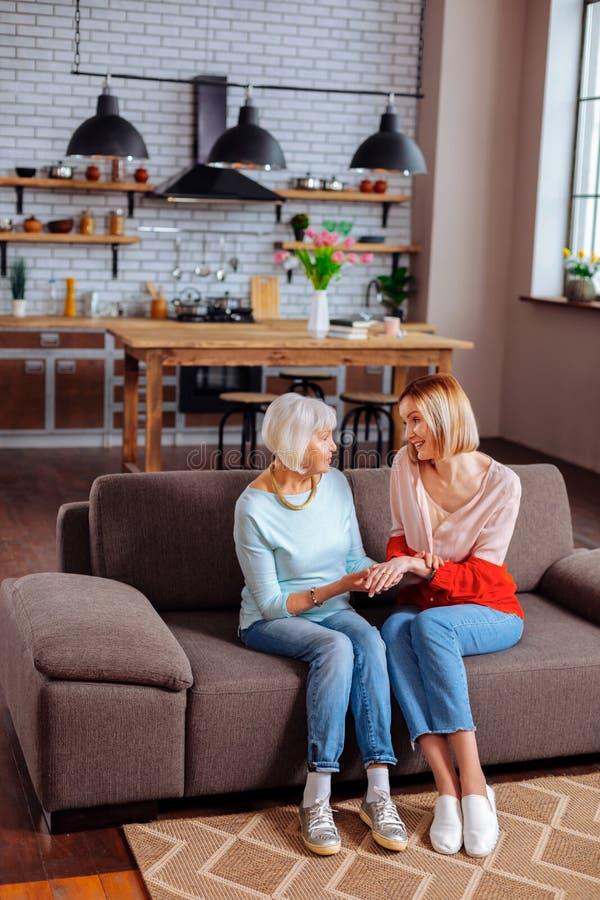 Bekymrad vuxen kvinna som lyssnar aktivt till grå färg-haired pensionärsamtal royaltyfri fotografi