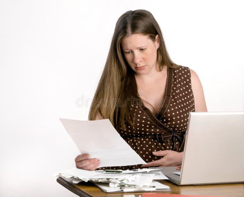 Bekymrade gravida läsningräkningar för ung kvinna på Lapt royaltyfri foto
