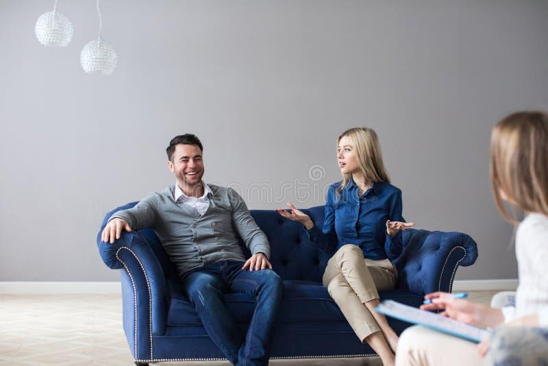 Bekymrade par som hemma lyssnar till psykologen under ett terapisammanträde på en soffa royaltyfria bilder