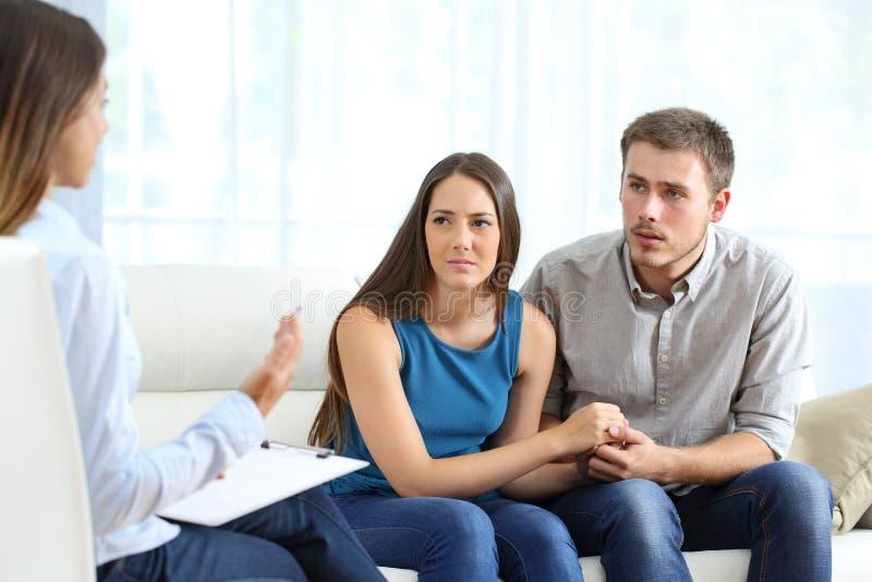 Bekymrade par som lyssnar till förbindelselägerledaren royaltyfria foton