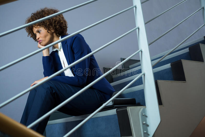 Bekymrat affärskvinnasammanträde på moment royaltyfri foto