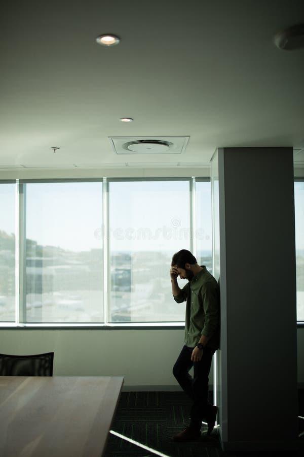 Bekymrat affärsmananseende vid fönstret arkivbild