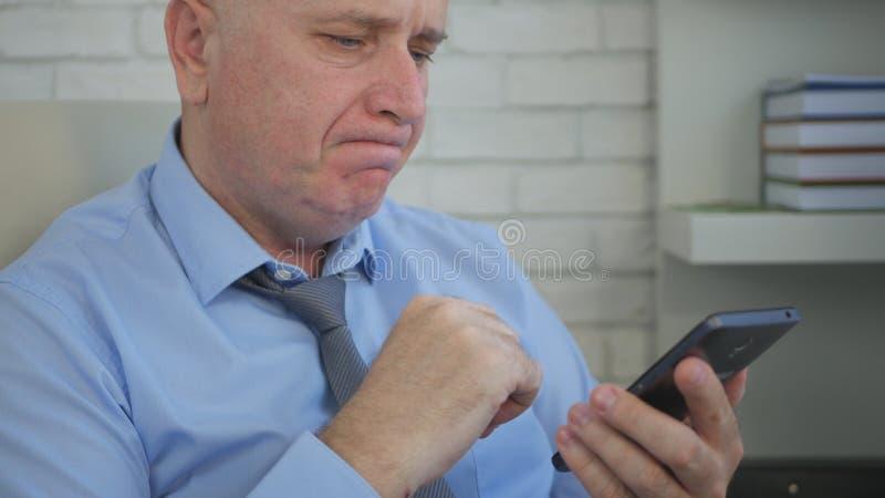 Bekymrat affärsmanImage In Office rum genom att använda mobiltelefonen arkivbild
