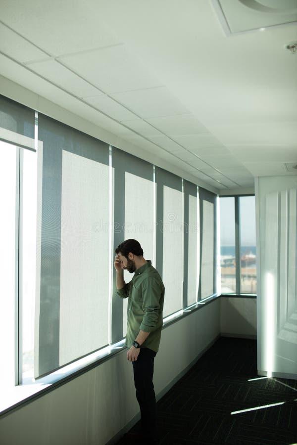 Bekymrat anseende för affärsledare vid fönstret i regeringsställning royaltyfri fotografi