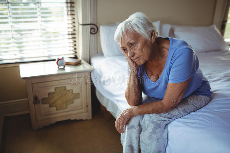Bekymrat högt kvinnasammanträde på säng i sovrummet royaltyfria bilder