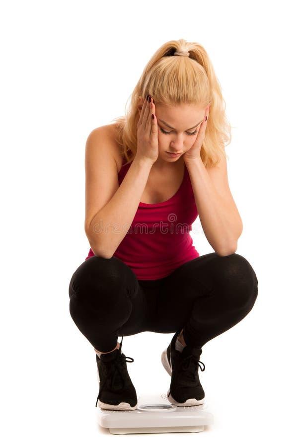 Bekymrat kvinnaanseende på skalan som mäter vikt arkivbild