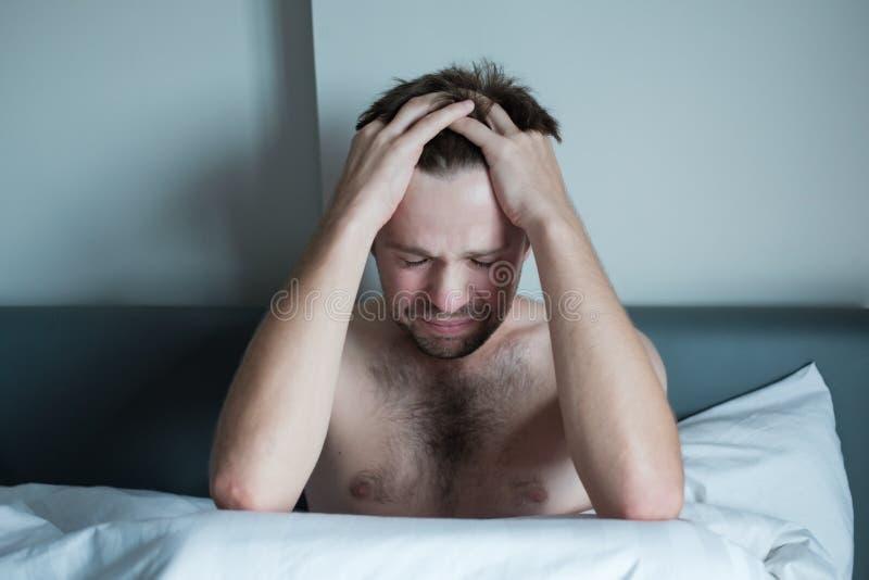 Bekymrat mansammanträde på säng med handen på pannan Han har problem med mentala hälsor och hör stämmor i hans huvud arkivbild