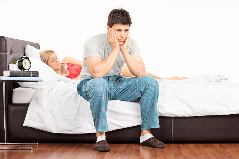 Bekymrat mansammanträde på säng och sova för flicka royaltyfri foto