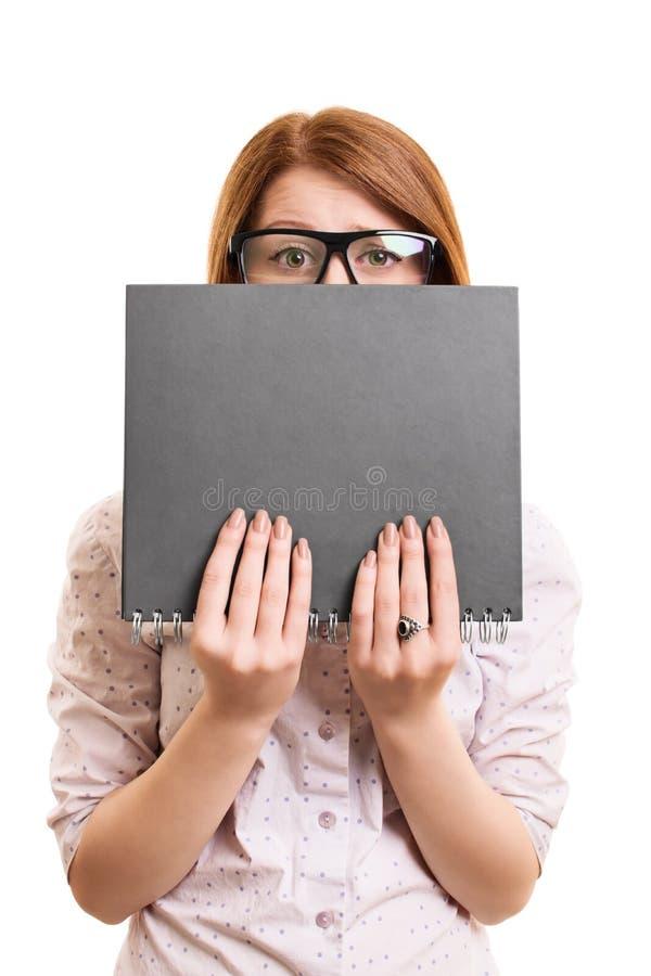 Bekymrat nederlag för kvinnlig student bak en bok arkivbilder