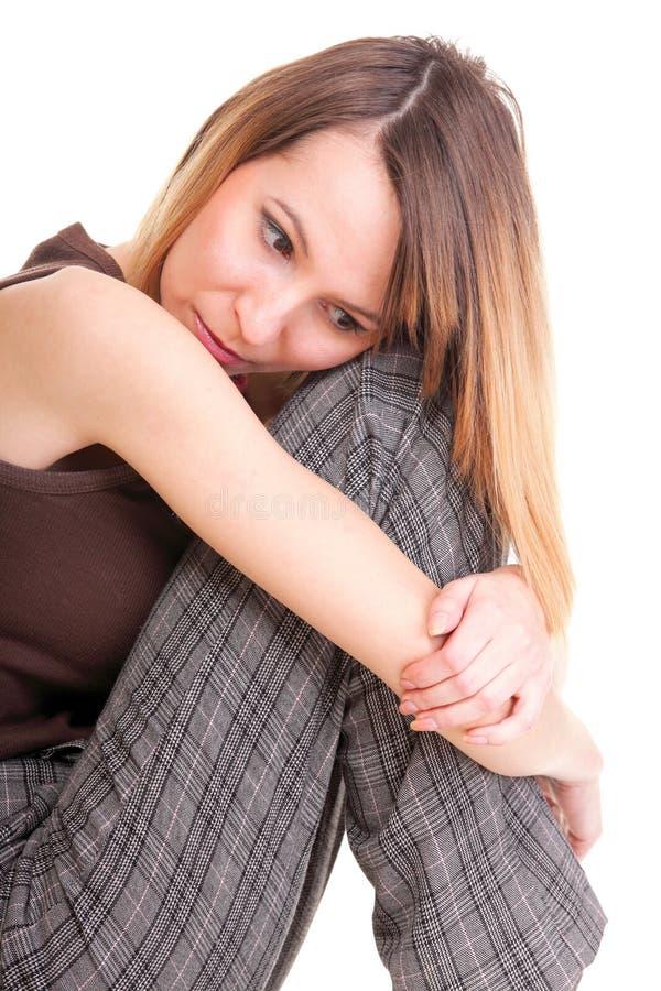 Bekymrat och räddt ungt kvinnasammanträde på stol. Isolerat arkivbild