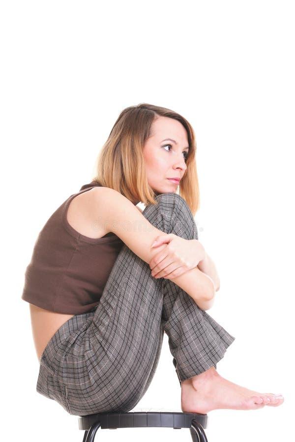 Bekymrat och rätt sammanträde för ung kvinna på stol. Isolerat royaltyfri foto