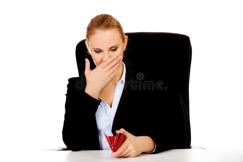Bekymrat sammanträde för affärskvinna bak skrivbordet med den tomma plånboken royaltyfria bilder