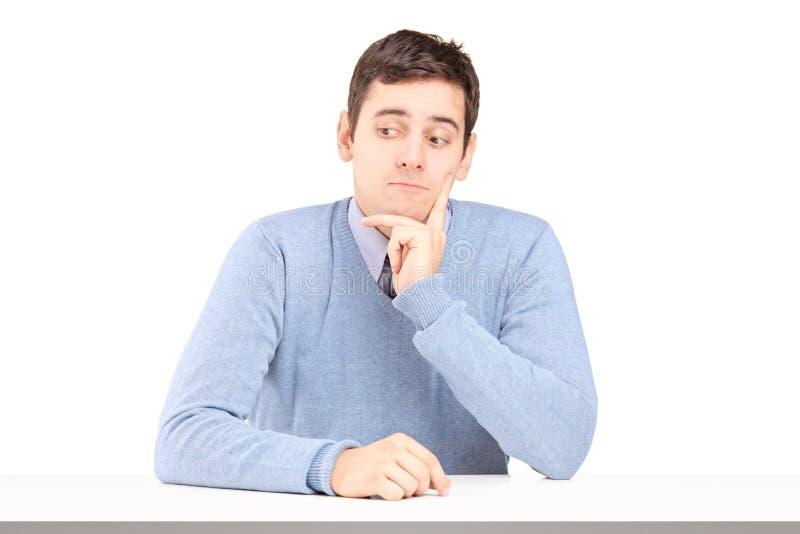Bekymrat sammanträde för ung man på ett skrivbord royaltyfria foton